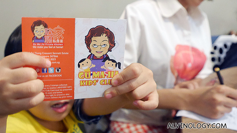 Asher flashing the Gu Ma Jia Kids' Club member card which will entitles him to discount and a S$5 voucher upon sign-up by parents