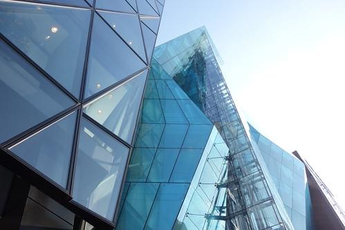 "Shibuya_23 渋谷の明治通りに面した所にある高層ビルディングを撮影した写真。 右の ""THE ICEBERG ビルディング"" の前面はターコイズブルー色のガラス張りで複雑な三次元ジオメトリック構造をしている。 左の ""J6Frontビル"" は前面が数多の三角形のガラス張りである。"