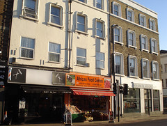 "A photo taken in winter sunlight, showing a four-storey building with three shopfronts along the ground floor.  The leftmost is in black and grey, and has a barber's pole and two images of scissors-plus-comb above, but no actual name on the frontage aside from ""Kodo's Barber"" in small letters on the edge of a protruding canopy.  The one in the middle has a fully open shopfront with vegetables displayed toward the front, and a sign reading ""African Food Centre"" above, in black letters on a bright orange background.  The one to the right is double-width and all in white with large windows; the sign reads ""White Sands""."