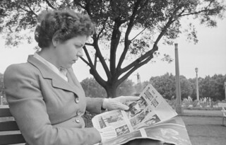 Sue Strizic sitting on park bench reading a magazine