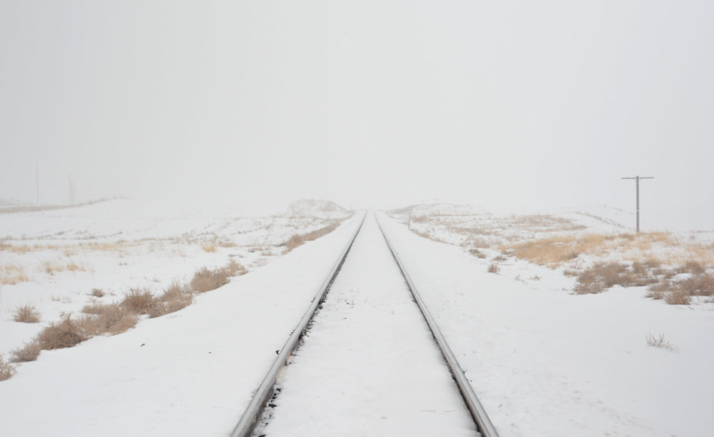 Train tracks disappearing into snow
