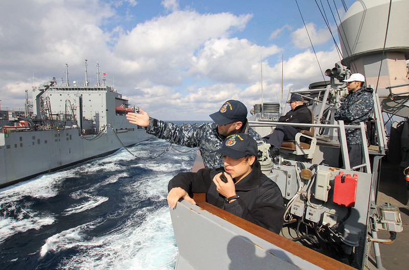 EAST CHINA SEA - Lt. Benjamin Pearlswig and Ens. Kathleen McDowell, conning officers aboard the USS John S. McCain communicate with the Military Sealift Command dry cargo and ammunition ship USNS Washington Chambers during a replenishment-at-sea.