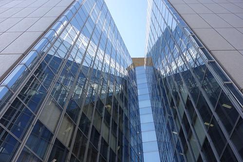 """Shibuya_3 渋谷で撮影した高層ビルディングの写真。 """"シオノギ渋谷ビル""""。 ビルディングの正面を撮影したもの。 鋭角に向かい合ったガラス張りの面に太陽光が反射を繰り返して放射状の光を放っている。"""