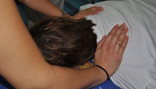 Sesión de trabajo con reiki en un paciente al que se le imponen las manos para transmitirle energía
