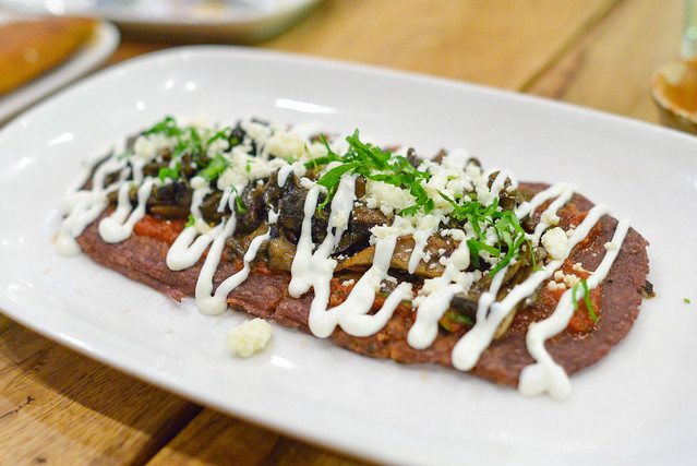 Huarache de Huitlacoche y Hongos Oval-shaped blue corn tortilla, pinquito beans, corn truffle, mushrooms, onion, jalapeño, fresh epazote, queso fresco, crema and salsa chiltomate