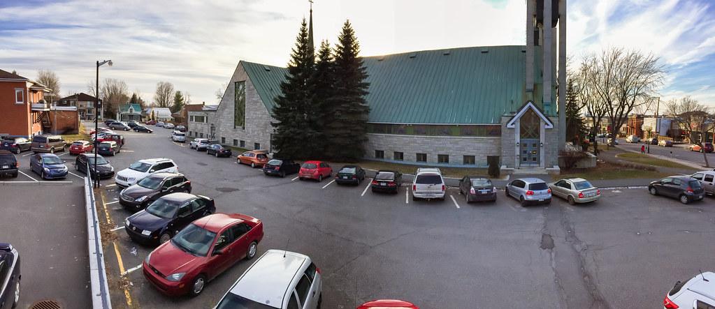 Vue de l'église Saints-Martyrs-Canadiens, du presbytère avoisinant ainsi que des rues Notre-Dame Est et St-Jean-Baptiste, qui délimitent le terrain.