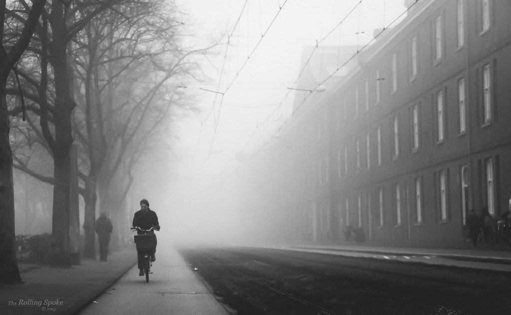 Bicycle riding through fog in Amsterdam