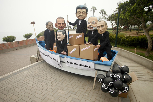 Activists wearing masks of world leaders in a boat