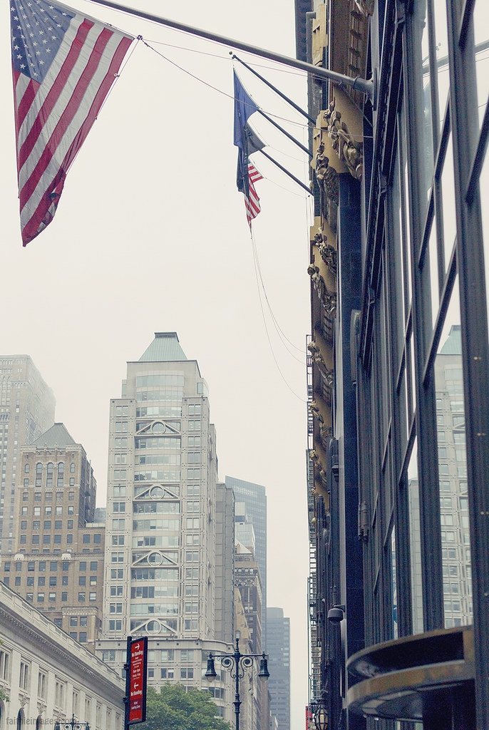 American flags and grey buildings