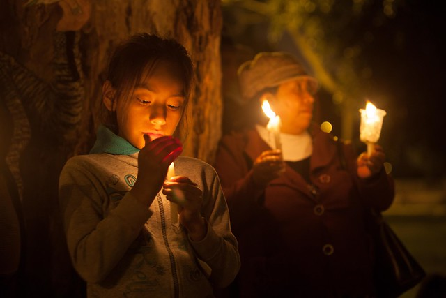 a little girl and a woman stand under a tree holding candles