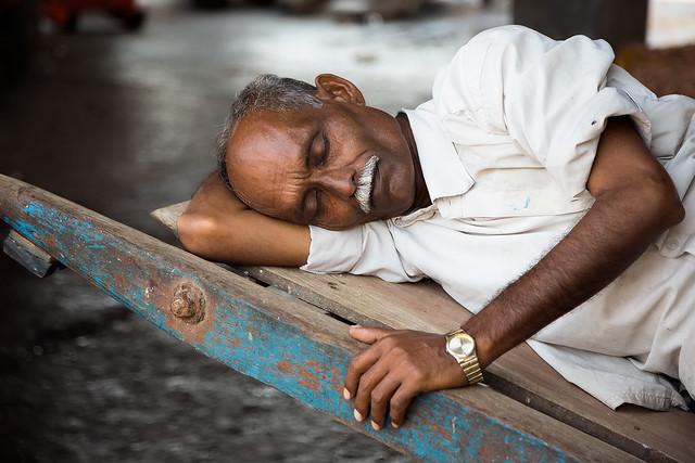 Sleeping man at the train station in Mumbai, India.