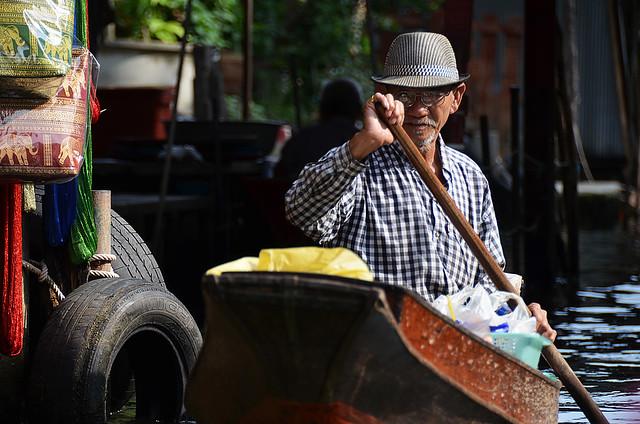 Señor tailandés remando con su barca por los canales de Damnoen Saduak