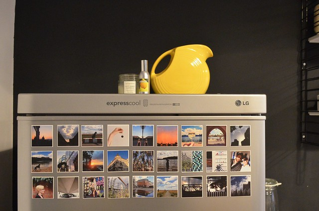 Berlin apartment_ kitchen refrigerator with Instagram magnets and Fiestaware pitcher against black wall