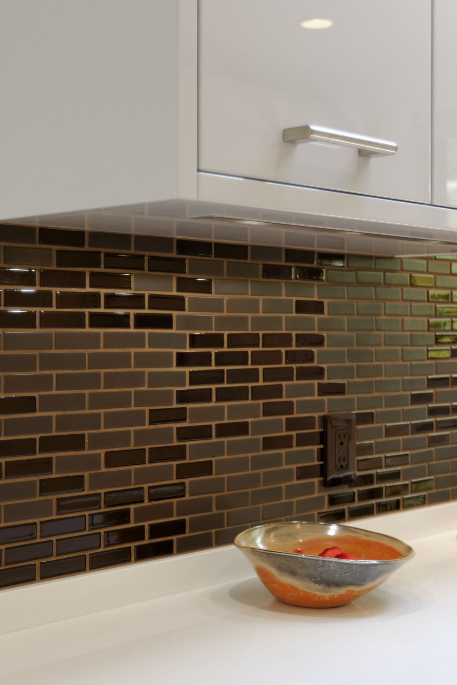 By having a mix of tile sheen, the light seems to play and backsplash appears to have movement.