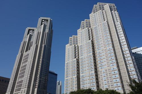 "Shinjuku_12 ""東京都庁第一本庁舎"" と ""第二本庁舎"" のビルディング写真。 青空を背景にして南西からの陽射しを受けて輝いている。"