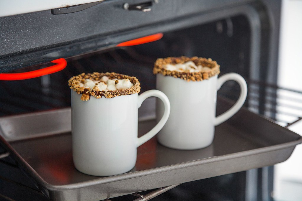 two mugs of hot cocoa on a tray in the oven
