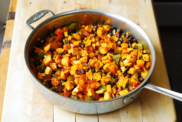 Adding butternut squash to the skillet with beans, corn, bell peppers, all clad frying pan, skillet