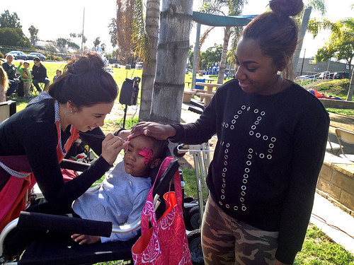 SAN DIEGO - Personnel Specialist 3rd Class Carchelle Bethel (right) watches as her daughter, Marley Bethel, gets her face painted during a children's holiday party hosted by the amphibious transport dock ship USS New Orleans (LPD 18).