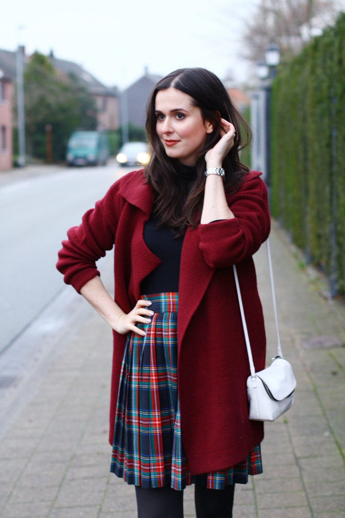 pleated plaid skirt, burgundy cardigan, white cross body bag
