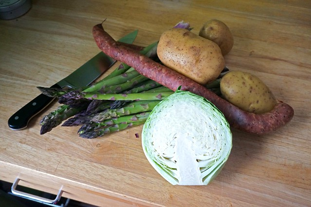 A pile of vegetables: bright green asparagus wiht deep purple tips, with three tawny brown potatoes covering their stem ends, a vibrant red sausage link lying across, and a half of a cabbage in the foreground, it's pale green leaves crinkled against each other. There's a conscious resemblance to Renaissance still life painting
