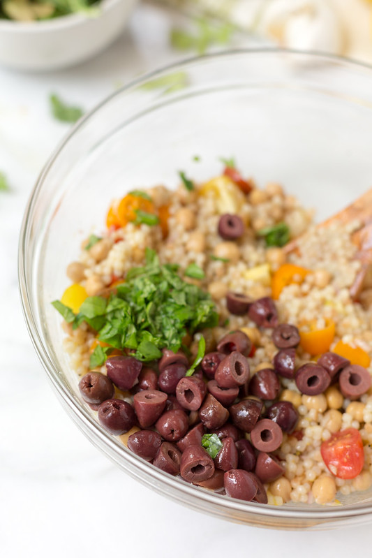 Adding the olives and basil to couscous salad