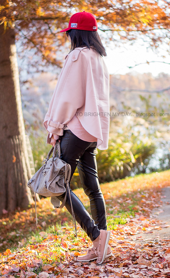 red cap, pink trench cape coat, striped shirt, black faux leather pants