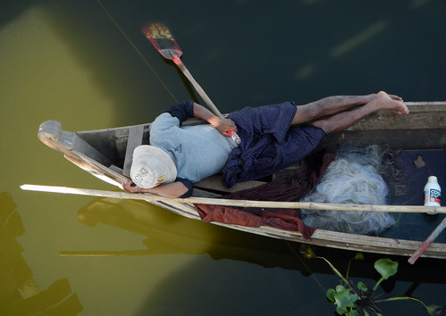 Napping after fishing in a boat by U Bein Bridge in Mandalay, Myanmar