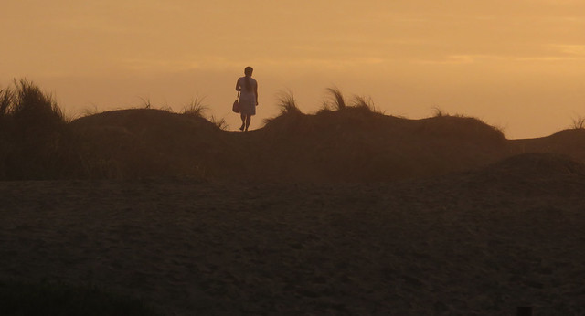 Woman walking in dunes at sunset on Ocean Beach, San Francisco; December 9, 2014