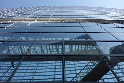 "Tokyo_26 東京都丸の内の ""東京国際フォーラム"" の写真。 見上げる角度で撮影したもの。 全面ガラス張りの壁面から建物の中が透けて見える。 施設内の空中通路が画像に写っている。 建物反対側の空が透けて見えている。"