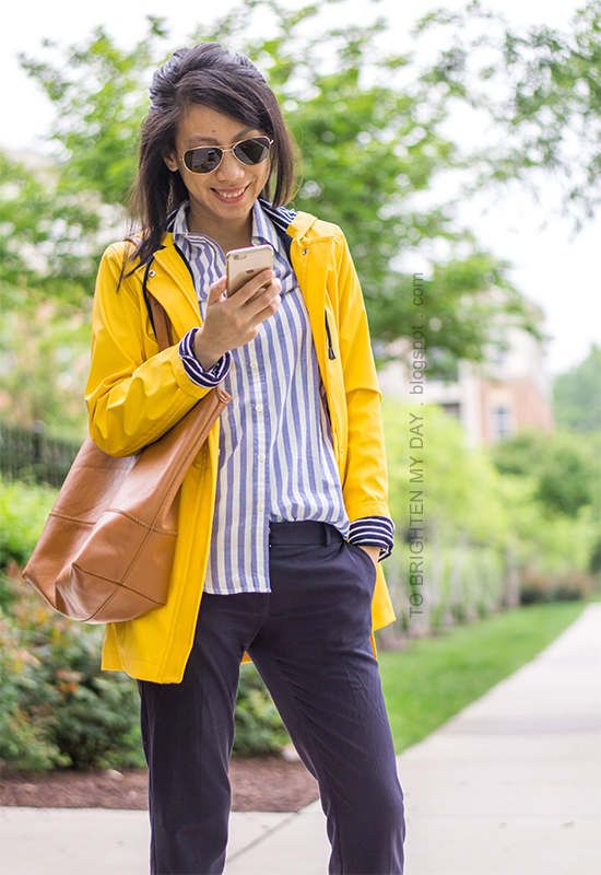 yellow rain coat, blue striped button up shirt, navy pants, cognac brown tote