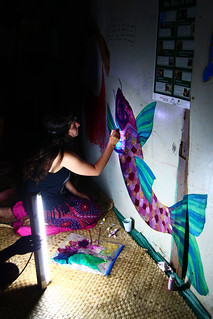 Bethany paints a coy fish on the wall by halogen light (Nakavika, Fiji)