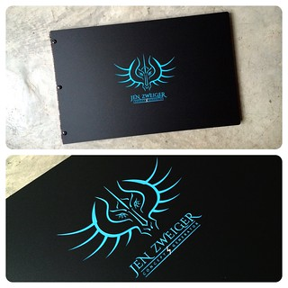 Custom graphic design portfolio book with engraved color fill treatment in blue on matte black acrylic