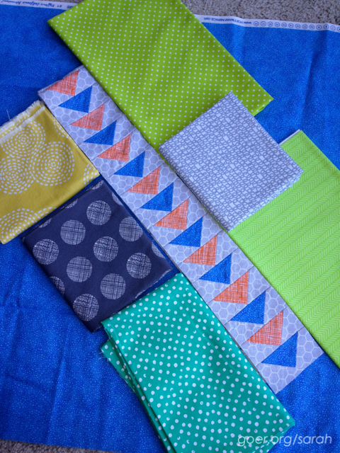yellow, grey, lime and sea green sample fabrics to potentially pair with orange and blue geese