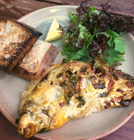 Omelette with kale, mushrooms, olives and bacon