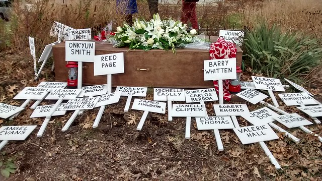 An empty coffin and name plaques are laid to rest at the memorial plot for homeless activist Mitch Snyder: a final testament to deaths of people experiencing homelessness in 2014.   Photo by Reginald Black