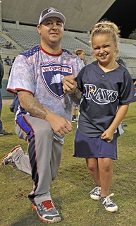 Coast Guard Petty Officer 1st Class Robert D. Somers, a damage controlman at Air Station Clearwater, Fla., is shown with Rhylee Brown, a member of The Miracle League, at the 2nd Annual St Petersburg, Fla., Softball Series at Al Lang Stadium on Saturday, Dec. 6, 2014. VETSports team members work with organizations, such as The Miracle League, who cater to children with mental and physical disabilities. (U.S. Coast Guard photo by Seaman Meredith A. Manning)