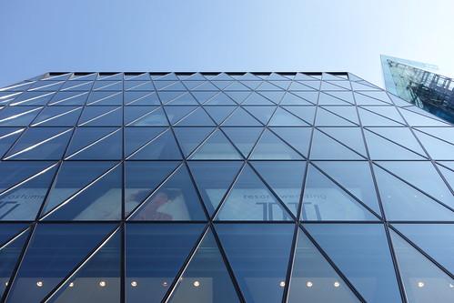 "Shibuya_20 渋谷の明治通りに面した所にある高層ビルディングを撮影した写真。 ""J6Frontビル""。 直下から見上げて撮影したもの。 前面が数多の三角形のガラス張りである。"