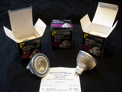 "Two small lightbulbs with two-prong fittings, on top of a receipt headed ""ABM Electrical Distributors Ltd"" for three ""MRCOB5CW, 5W COB MR16 LED LA"" at a total price of 29.70.  Three small boxes are in the background, two open, one closed."
