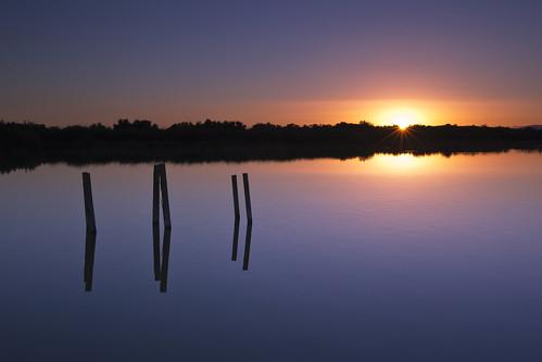 sunset sea reflection pier sticks colorful remains salton