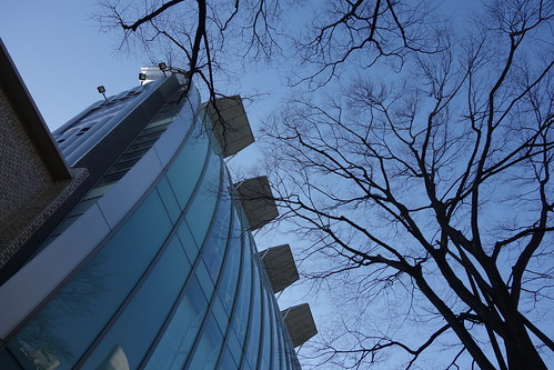 "Shibuya_15 表参道のビルディングを撮影した写真。 ""VELOQX 28 BULDING"" である。 建物前面の壁面は大きく湾曲したガラス張りとなっている。 上部は上方へ板状の蓋が開いた様な構造が4箇所設けられている。"
