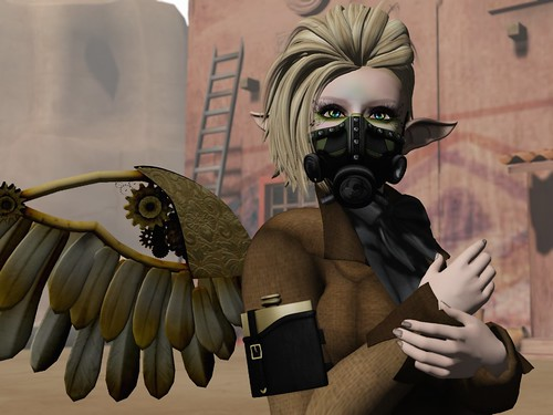 Image Description: Bust shot of a woman wearing a gas mask in front of an adobe style building.