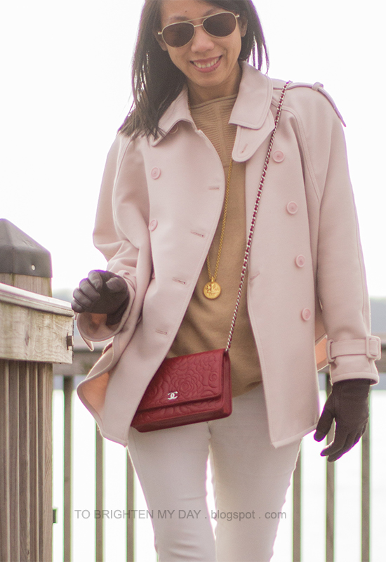 pink trench cape, camel sweater, burgundy/purple gloves, red crossbody bag, long necklace, white jeans