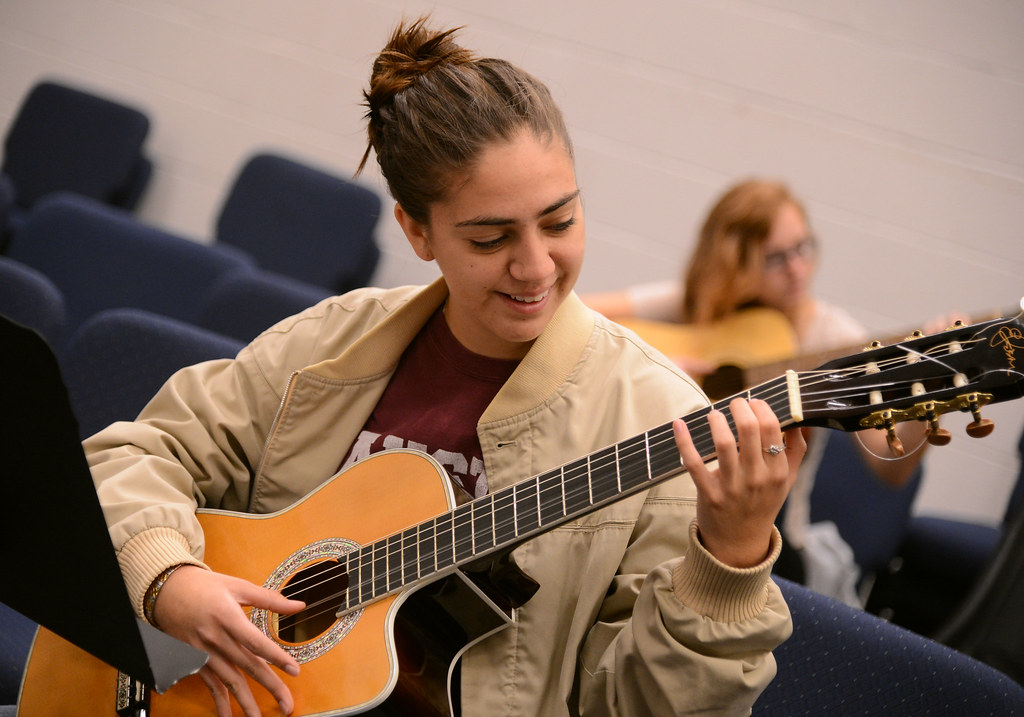 student stephanie gonzalez practices a song during a guitar class. Black Bedroom Furniture Sets. Home Design Ideas