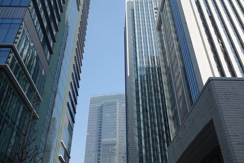 Tokyo_18 東京都丸の内の高層ビルディング群を撮影した写真。 左右に多数の高層ビルディングが林立している。 高層ビルディング同士の間から遠くの高層ビルディングが見える。