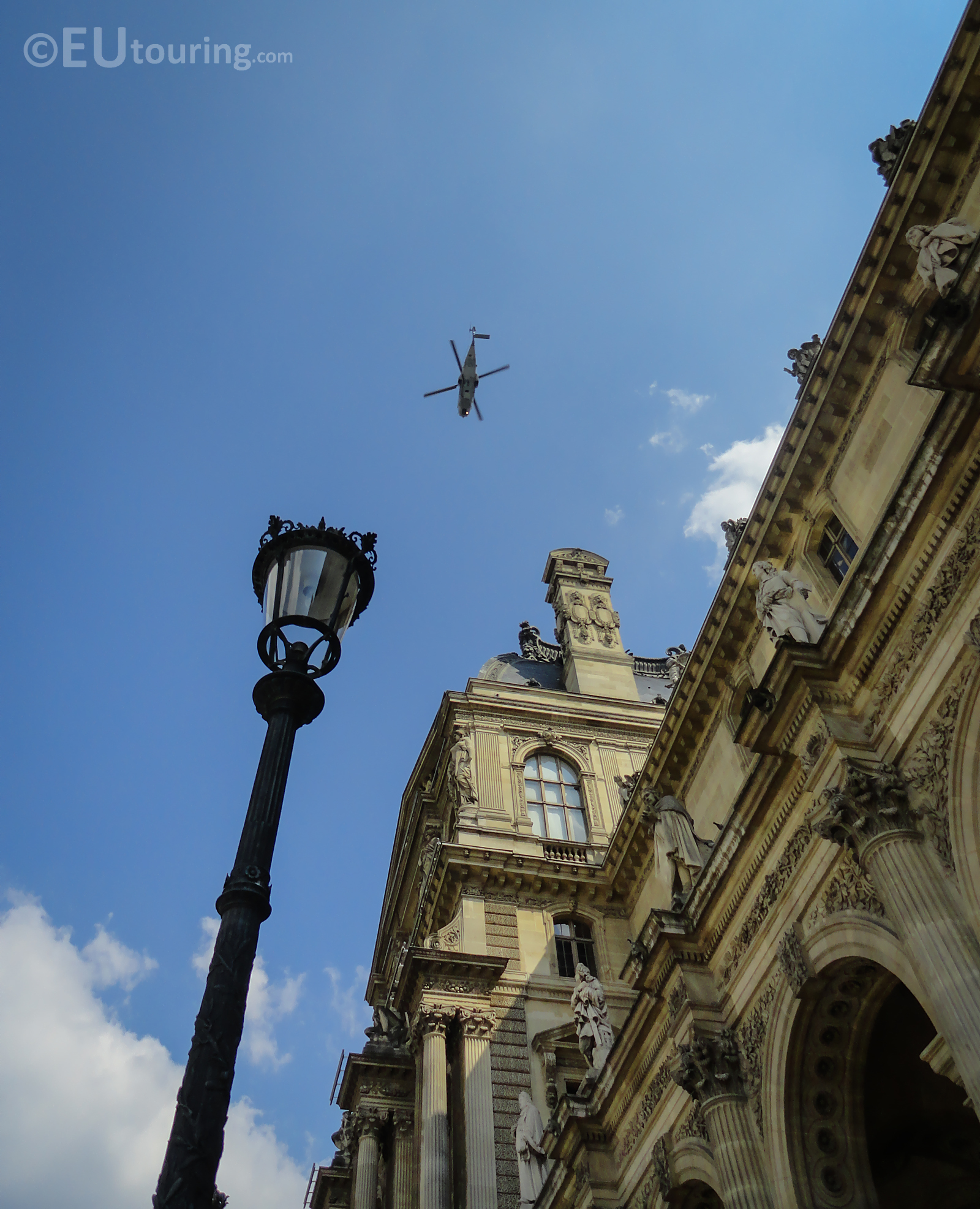 Helicopter passing over architecture of the Louvre