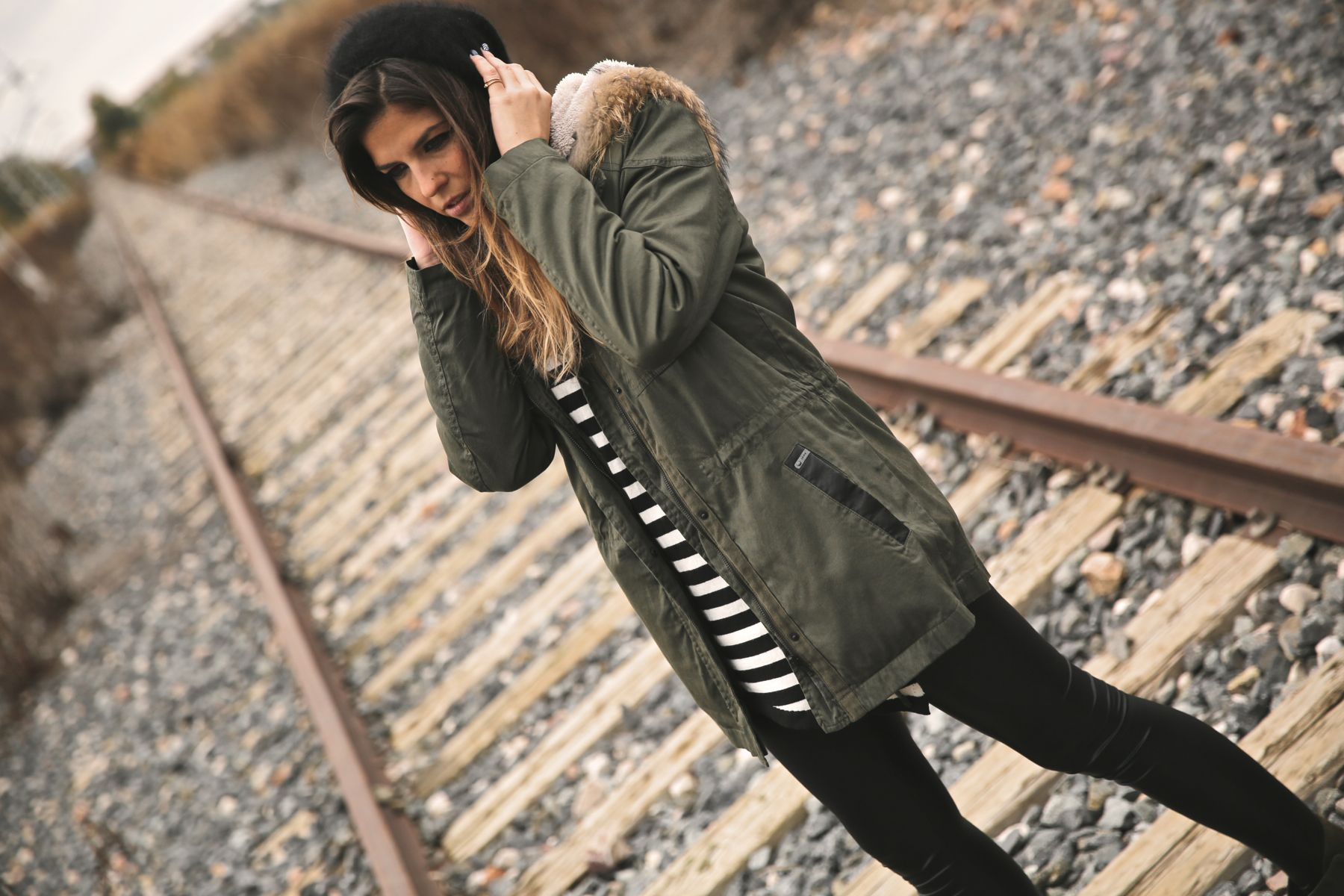 Look casual con parka, camiseta de rayas, gorro de lana y botines caqui