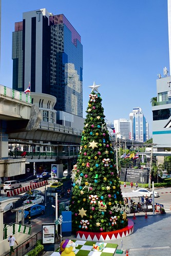 Christmas tree in front of Terminal 21 shopping centre on Sukhumvit road with Times Square building in Bangkok, Thailand