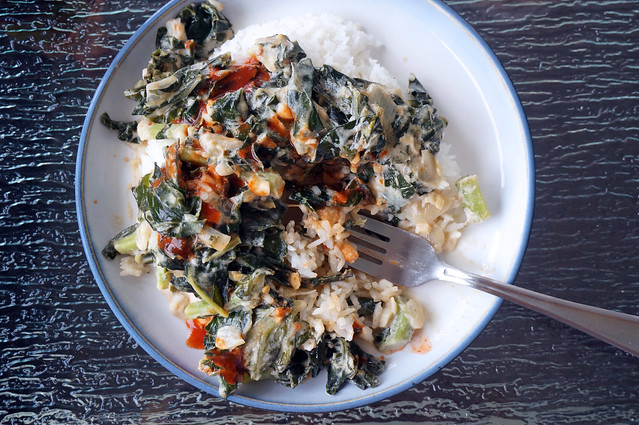 Collards with coconut and peanut butter, a fork resting among the dark green leaves with its tines disappearing into the pile of rice.