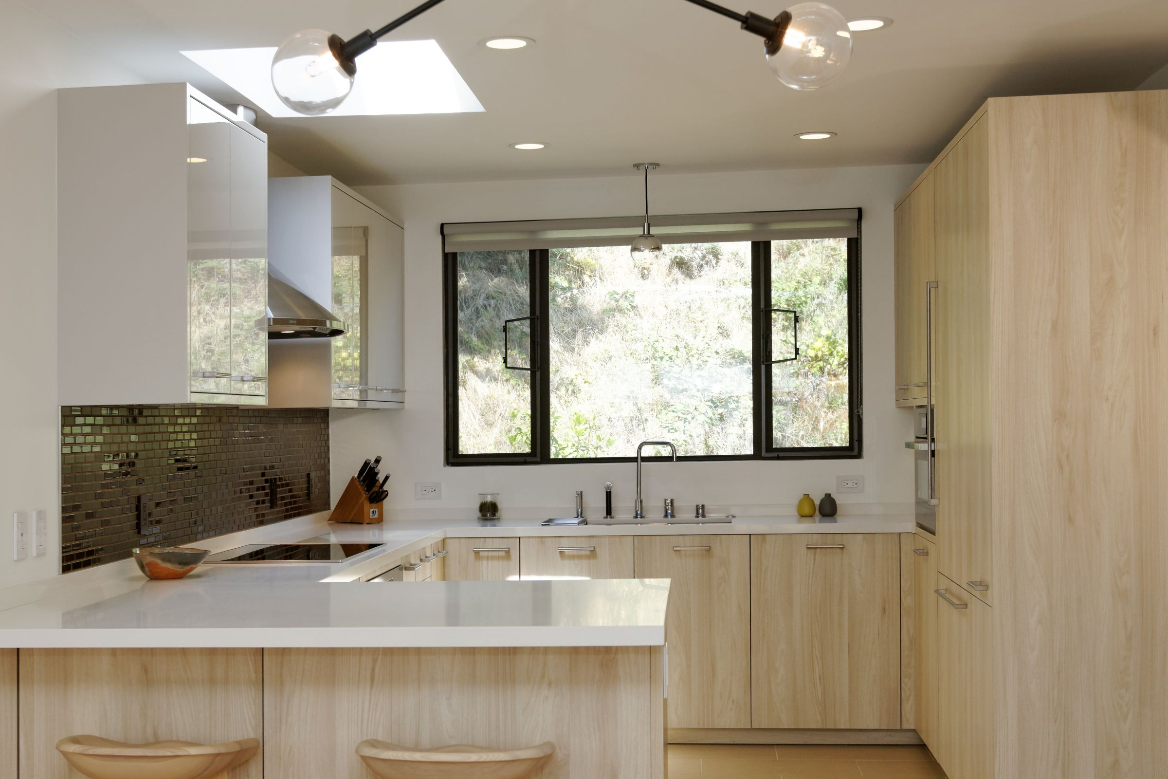 A mix of grain-matched light wood laminate and lacquer gives this kitchen a sophisticated enlightened appeal.