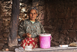 Berber lady by table in her mud hut home. Atlas Mountains